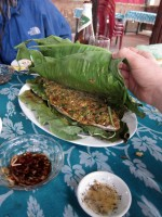Skinned flatfish wrapped in banana leaves and grilled over hot coals