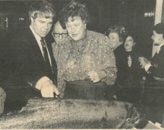"Cover of ""The Network"" printed by the Alaska Seafood Marketing Institute 4th quarter 1983   Caption reads:   Seattle Seafood Consultant Jon Rowely points out a monstrous white king salmon to Julia Child, America's best known cooking personality, at a New York dinner honoring the famed television chef. The salmon was donated by the Alaska Seafood Marketing Institute."
